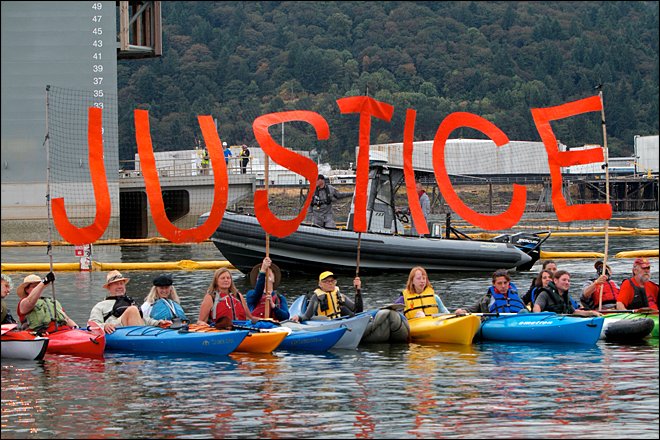 Environmental activists in kayaks protest the Fennica, a vessel that Royal Dutch Shell PLC plans to use in its Arctic offshore drilling project, as it underwent repairs on Swan Island, Saturday, July 25, 2015, in Portland, Ore.  The damaged ship, a 380-foot icebreaker, which arrived at a Swan Island dry dock early Saturday morning, is a key part of Shell's exploration and spill-response plan off Alaska's northwest coast. It protects Shell's fleet from ice and carries equipment that can stop gushing oil. (Sam Caravana/The Oregonian via AP) MAGS OUT; TV OUT; NO LOCAL INTERNET; THE MERCURY OUT; WILLAMETTE WEEK OUT; PAMPLIN MEDIA GROUP OUT; MANDATORY CREDIT
