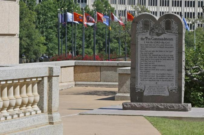 FILE - In this Tuesday, June 30, 2015 file photo, the Ten Commandments Monument is pictured at the state Capitol in Oklahoma City, Okla. The Oklahoma Supreme Court's June 30 decision to order the monument removed from the state Capitol grounds has so angered conservatives in the Legislature that some Republicans are calling for justices to be impeached. (AP Photo/Sue Ogrocki, File)