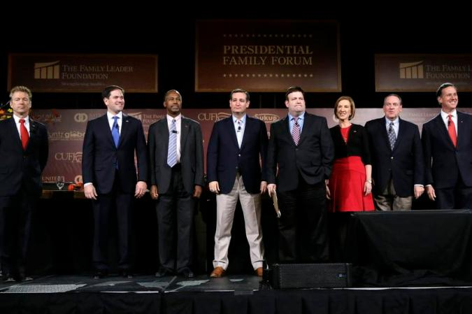 Republican presidential candidates, from left, Rand Paul, Marco Rubio, Ben Carson, Ted Cruz, moderator Frank Luntz, Carly Fiorina, Mike Huckabee and Rick Santorum stand on stage during the Presidential Family Forum, Friday, Nov. 20, 2015, in Des Moines, Iowa. (AP Photo/Charlie Neibergall)