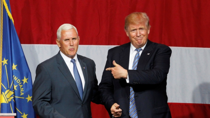 Republican U.S. presidential candidate Donald Trump (R) points to Indiana Governor Mike Pence (L) before addressing the crowd during a campaign stop at the Grand Park Events Center in Westfield, Indiana, July 12,  2016. REUTERS/John Sommers II - RTSHNAG